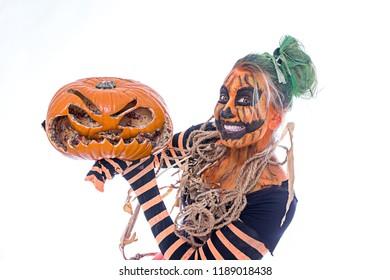 A pumpkin-clad woman is holding a rotten pumpkin