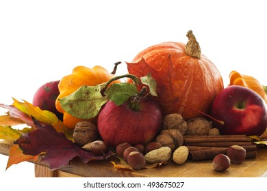 Pumpkins, apples and nuts over white background. Selective focus