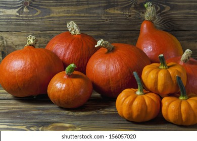 Pumpkins of different varieties and sizes on a wooden table