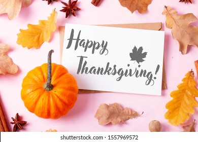 Pumpkins, fall leaves and spices on pink flat lay autumn background, with happy thanksgiving greetings on white blank greeting card