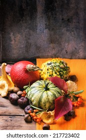 Pumpkins, nuts, berries and mushrooms chanterelle over old wooden table. See series