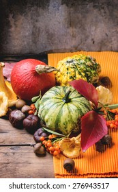 Pumpkins, nuts, berries and mushrooms chanterelle over old wooden table. See series.
