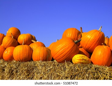 pumpkins on bales of straw against the blue cloudless sky