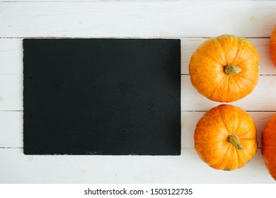 Pumpkins on wite wooden background and black slate stone surface. Thanksgiving and Halloween concept. View from above. Top view. Copy space for text and design
