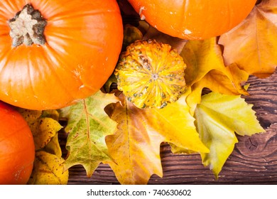 Pumpkins on a wooden table with autumn leaves