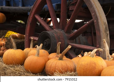 Pumpkins rest beside wagon wheel amidst hay