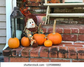 pumpkins with scarecrow and an old light on a brick porch in autumn in New England, lots of pumpkins on a front porch. autumn decorations on a front porch.
