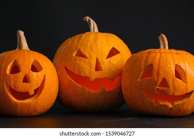 Pumpkins with scary faces on black background. Halloween traditional decor
