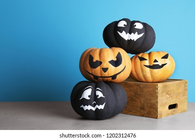 Pumpkins with scary faces on table against color background, space for text. Halloween decor