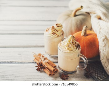 Pumpkins spice latte with pumpkins and withe cozy sweater over white wood texture. Copy space.