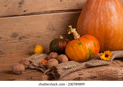 Pumpkins, walnut, quince, ear and burlap on wooden background