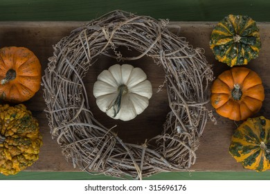 pumpkins in wreath on wooden surface
