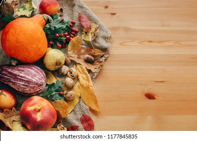 Pumpkin,vegetables ,colorful leaves with acorns and nuts on wooden table. Bright Fall image. Harvest time. Happy Thanksgiving flat lay. Hello Autumn.