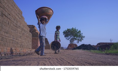 Puna / India - March 15, 2019: Indian poor child labors working in a brick factory,  an unhappy little girl working with her brother. extreme poverty in India