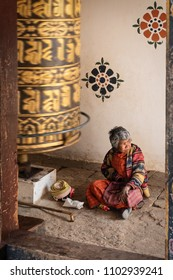 Punakha, Bhutan - April 1, 2018 : Old woman at the Chimi Lhakhang temple, sitting near a giant prayer wheel