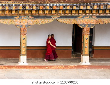 Punakha, Bhutan - April 30, 2018: Two buddhist monks walk in the courtyard of the Punakha Dzong, a 17th century fortress in Punakha, Bhutan.