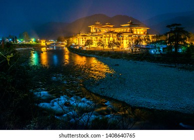 Punakha, Bhutan - March 1, 2015. Magnificent view of Punakha Dzong at the riverside baths in golden lights at blue hour. Punakha Dzong is considered one of the most beautiful Dzongs in Bhutan.