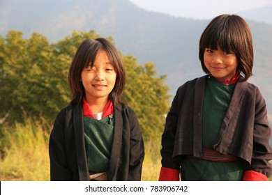 PUNAKHA, BHUTAN - NOVEMBER 23, 2017: Colorfully-dressed students on their way to school in rural Bhutan.