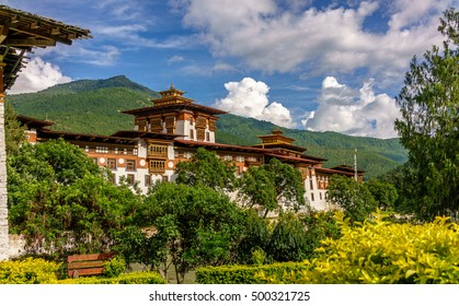 Punakha Dzong behind the river with a blur foreground of yellow leaves plants and blur background of mountains in Bhutan, on September 20 2016.