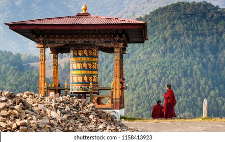 Punakha/Bhutan - March 1, 2016:  young women monks of the Buddhist monastery in their traditional red robes before classes next to the prayer wheel against the background of the Himalayan mountains