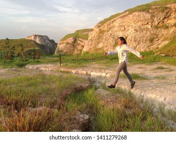 PUNCAK ALAM HILLPARK, MALAYSIA - MAY 2019 : A happy girl running on grassy hill in the park, laughing & jumping.