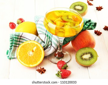 punch in glass with fruits, on white wooden table