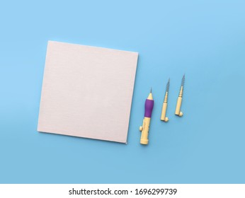 Punch needle embroidery concept with a blank fabric frame as a mockup and punch needle with spare pricks, top view do it yourself (DIY) project tools  on blue background