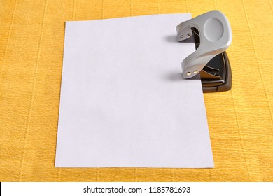 Puncher is used to perforate blank sheet of paper, yellow background.