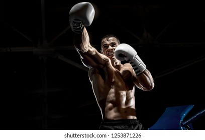 punching boxer on boxing ring, black background, horizontal photo