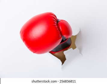 Punching boxing glove though over paper wall