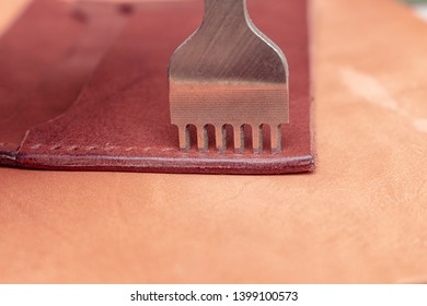 Punching holes in a leather wallet with line piercer diamond shape puncher tool before stitching handmade leathercraft