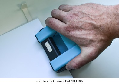 Punching holes in sheet of paper, using steel hole puncher, close-up of hand