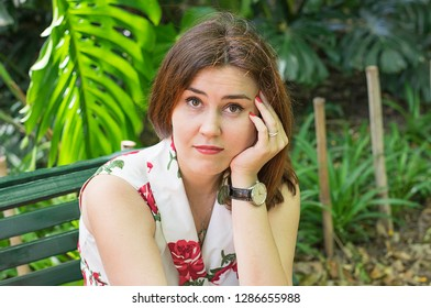punctual girl or woman  with the clock is waiting for someone in the park with a discontented face