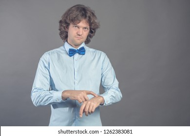 Punctual serious man points at wrist, being worry as lates for meeting wears blue shirt and bow tie stares straiht at camera and lightly smiles. Guy checks time over grey background. Time out concept