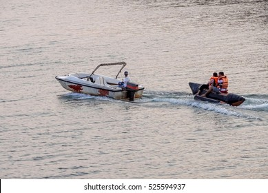 Pune / India - April 13, 2013 - Couple enjoying the banana boat ride in Panshet lake water when pulled and drifted along with the motor / speed boat