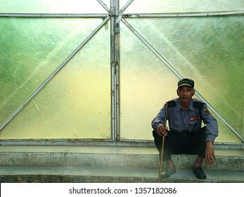 Pune, India - August 28 2004: A security guard sitting in front of a closed gate at Pune India.