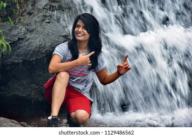 Pune, India - July 08 2018: Candid portrait of a young lady at a waterfall at Lonavala near Pune India.