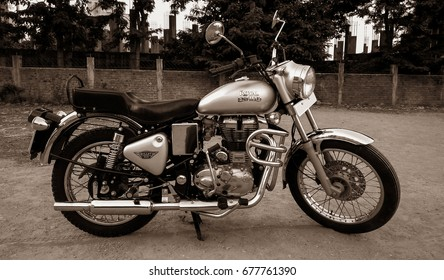 Pune / India - May 01, 2017 - Classical Royal Enfield Bullet Electra 350 bike parked on the rough road with a retro vintage instagram old style filter effect.