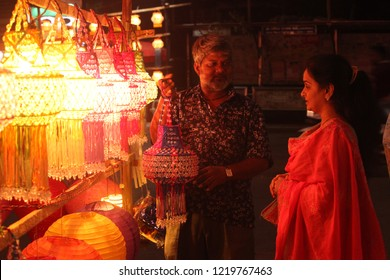 Pune, India - November 2018: An Indian shopkeeper selling his beautiful lantern to a woman shopping for Diwali festival, in India.
