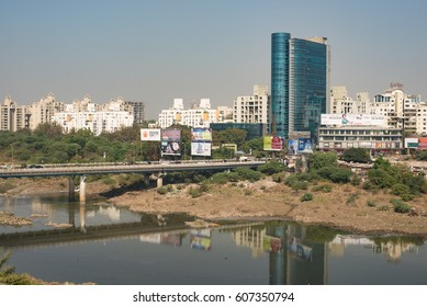 PUNE, INDIA - November 22, 2016: Traffic, billboards, and skyline over the Mula Mutha River