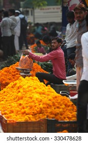 Pune, India - October 21, 2015: A seller weighing a bag of marigold flowers before selling it in his streetside shop, on the eve of Dassera festival in India