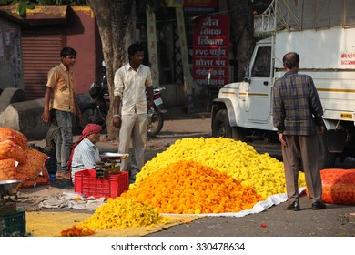 Pune, India - October 21, 2015: A man selling marigold flowers to a customer on the streetside in India, on the eve of Dassera festival