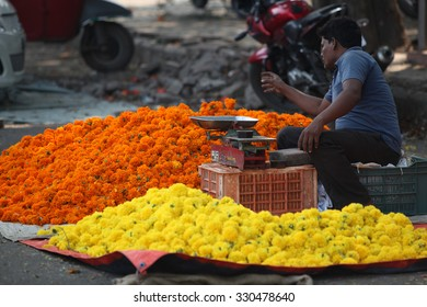Pune, India - October 21, 2015: A man setting up his marigold flower shop on the streetside in India, on the eve of Dassera festival