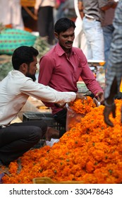 Pune, India - October 21, 2015: A streetside flower seller packing Marigold flowers for a customer on the eve of Dassera festival in India in which these flowers are traditionally used.