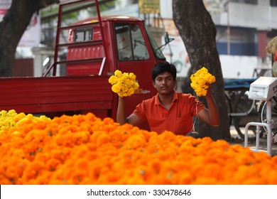 Pune, India - October 21, 2015: A man shows off his fresh marigold flowers in his streetside shop in India, on the eve of Dassera festival