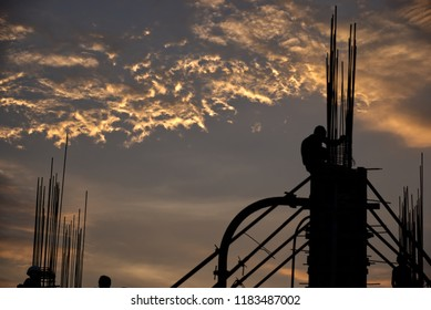 Pune, India - September 19 2018: Construction workers silhouetted against the setting sun at Pune India.