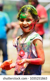 PUNE, MAHARASHTRA, INDIA, 24 March 2016. A young girl with colored powder on her face celebrating holi festival