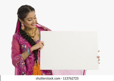 Punjabi woman holding a blank placard and smiling