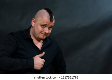 Punk in a black shirt. The finger of the hand shows upward. The look is sly and interrogative.
