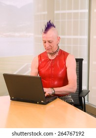 Punk Businessman - Older man with purple mohawk wearing red PVC and spiked collar working on a laptop at a boardroom table.